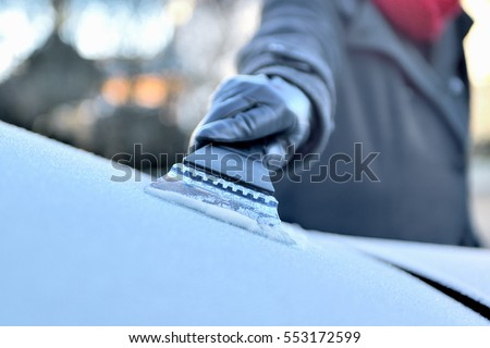 Winter Driving - Woman is scraping Ice from the frozen windows of her car #553172599