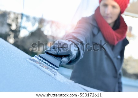 Winter Driving - Woman is scraping Ice from the frozen windows of her car #553172611