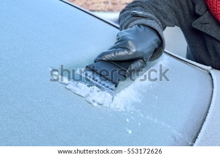 Winter Driving - Woman is scraping Ice from the frozen windows of her car #553172626