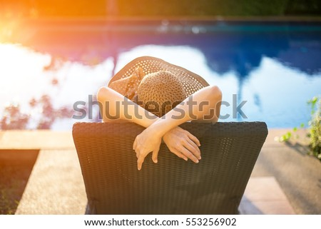 Summer day lifestyle woman relax and chill near luxury swimming pool sunbath at the beach resort outdoors the hotel.  Vacations and Summer Concept Royalty-Free Stock Photo #553256902