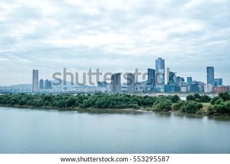 modern office buildings near river in seoul in cloud sky #553295587