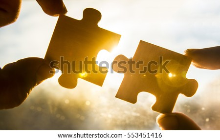 two hands trying to connect couple puzzle piece with sunset background. Jigsaw alone wooden puzzle against sun rays. one part of whole. symbol of association and connection. business strategy.  #553451416