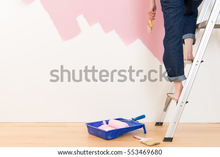 Beautiful young woman standing on ladder doing wall painting. mixed race asian chinese female model Royalty-Free Stock Photo #553469680