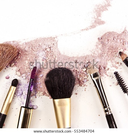 Makeup brushes, lipstick and pencil on a white background, with traces of powder and blush on it. A square template for a makeup artist's business card or flyer design; with copyspace