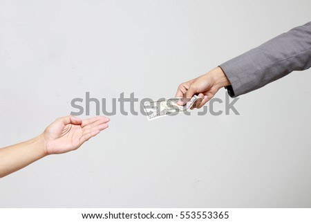 Businessman hand holding US dollar, USD. bills, offers dollar bank note money and giving money Paid for Something by Cash in Business Concept. #553553365