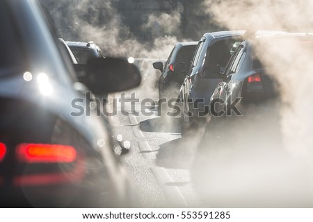 Blurred silhouettes of cars surrounded by steam from the exhaust pipes. Traffic jam  Royalty-Free Stock Photo #553591285