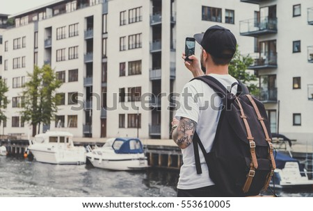 Young hipster man with backpack, taking pictures of street on smart phone at journey in Copenhagen, city tourism, warm colors #553610005