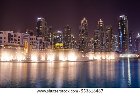 Dubai skyscrapers and dancing fountain in the evening #553616467