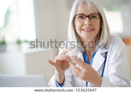 Senior female doctor giving prescription to patient #553625647