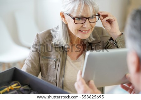 Senior woman in optical store trying eyeglasses on #553625695