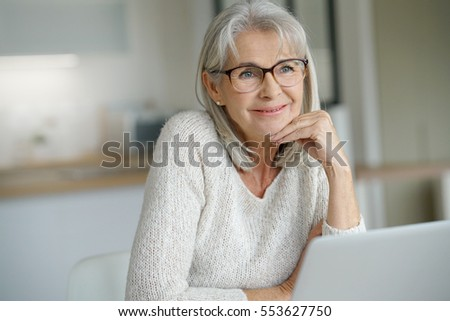 Senior woman at home websurfing on laptop computer #553627750