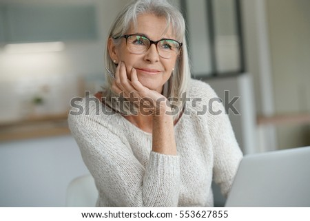 Senior woman at home websurfing on laptop computer #553627855