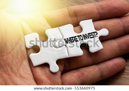 WHERE TO INVEST written on White color of jigsaw puzzle with hand,conceptual