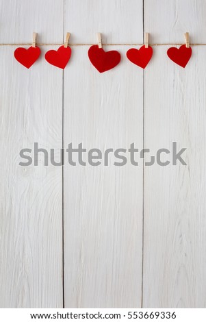 Valentine background with red paper hearts row border on clothespins on white rustic wood planks. Happy lovers day card mockup, copy space #553669336