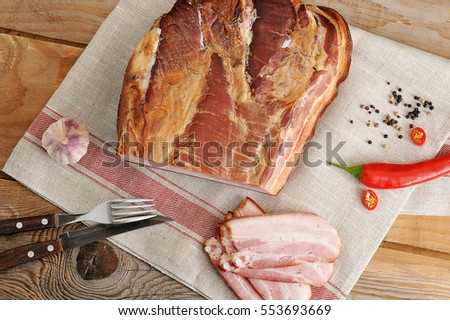 a piece of smoked pork - loin on a linen napkin with chili and spices on rustic wooden background - top view #553693669