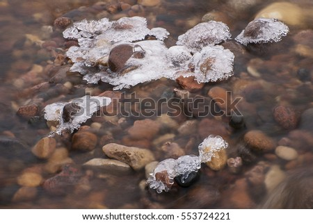 Ice and snow formations on stones in water #553724221