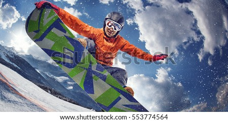 Sport background. Winter sport. Snowboarder jumping through air with deep blue sky in background. Royalty-Free Stock Photo #553774564
