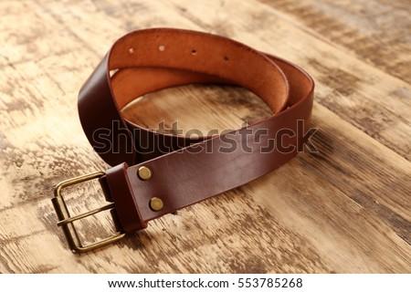 Stylish leather belt on wooden background Royalty-Free Stock Photo #553785268