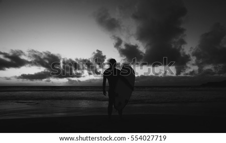Silhouette of young male surfer standing at the beach and holding surfboard at sunset against blue sky with clouds background. #554027719