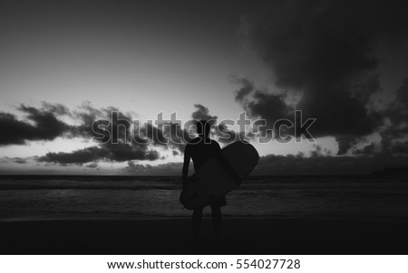 Silhouette of young male surfer standing at the beach and holding surfboard at sunset against blue sky with clouds background. #554027728