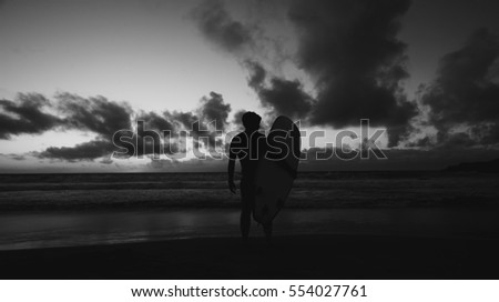 Silhouette of young male surfer standing at the beach and holding surfboard at sunset against blue sky with clouds background. #554027761