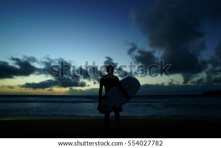 Silhouette of young male surfer standing at the beach and holding surfboard at sunset against blue sky with clouds background. #554027782