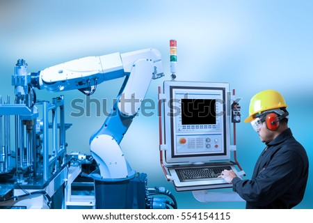 Industry concept and blue tone of engineer use control panel programing automated robot arm in production line of smart factory  #554154115