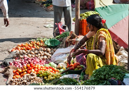 The colorful of fresh open air Gulmandi local market. Woman selling vergetables on street side walk. This is one of the largest bazaars in Aurangabad, India. #554176879