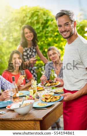 On the terrace in front of the table where his friends are gathered a handsome man with gray hair presents to the camera the dishes of meats and vegetables he has just prepared. Shot with flare #554194861