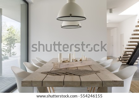 Room with wood dining table, white chairs and industrial lamp Royalty-Free Stock Photo #554246155