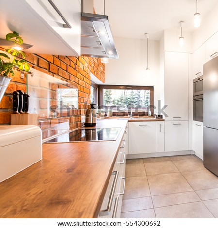 Spacious stylish kitchen with white units, wooden wheat, marble floor and red brick wall #554300692