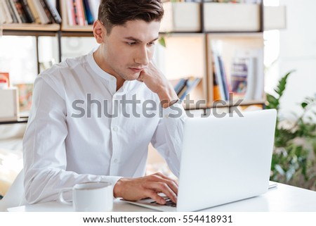 Photo of concentrated man dressed in white shirt using laptop computer. Coworking. Look at laptop. #554418931