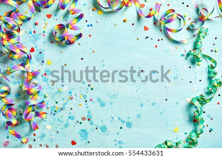Festive party or carnival border of coiled streamers and confetti on a light blue green wood background with copy space