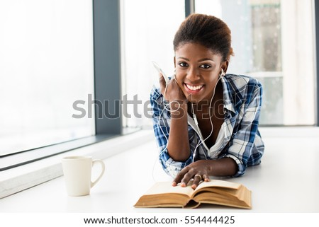 smiling young black woman, listening music from her cellphone, lying on the floor and relaxing next to a window with a book in front and a cup of coffee, looking to camera #554444425