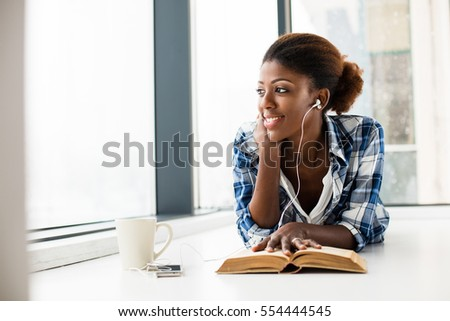 young beautiful black woman lying on the floor reading a book and listening music at her cellphone with a cup of coffee next #554444545