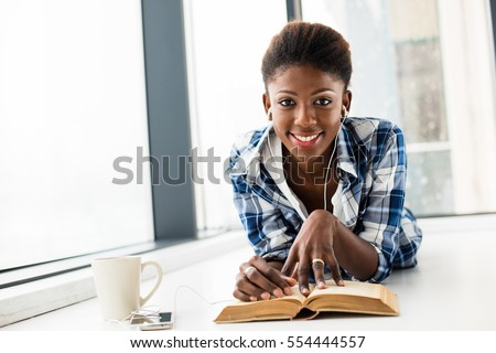 smiling young black woman, listening music from her cellphone, lying on the floor and relaxing next to a window with a book in front and a cup of coffee, looking to camera #554444557