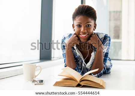 smiling young black woman, listening music from her cellphone, lying on the floor and relaxing next to a window with a book in front and a cup of coffee, looking to camera #554444614