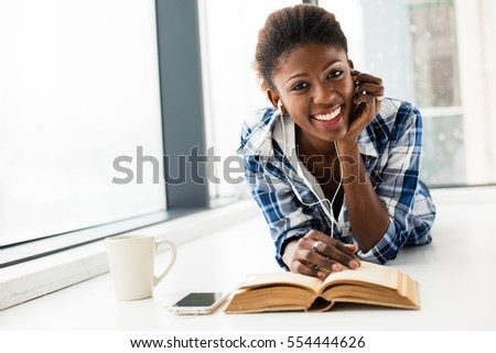 smiling young black woman, listening music from her cellphone, lying on the floor and relaxing next to a window with a book in front and a cup of coffee, looking to camera #554444626