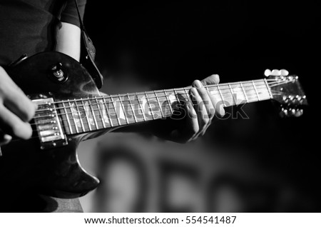 Guitar neck close-up on a concert of rock music in the hands of a musician #554541487