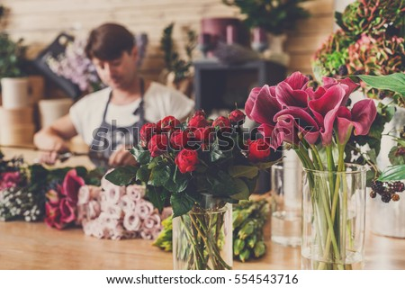 Small business. Male florist unfocused in flower shop. Floral design studio, making decorations and arrangements. Flowers delivery, creating order #554543716