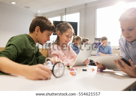education, science, technology, children and people concept - group of happy kids or students with tablet pc computer programming electric toys and building robots at robotics school lesson Royalty-Free Stock Photo #554621557