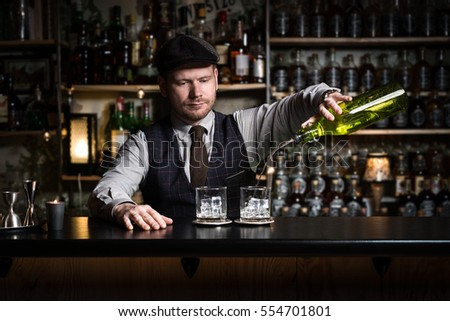 Bartender bartender is pouring a drink and looking at the camera #554701801