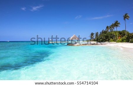 View of a beach under a blue sky with some clouds and a turquoise sea above a picturesque, tropical island.  #554714104