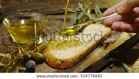 Genuine Italian organic oil cold pressed in slow motion falls on organic bread. concept of nature and healthy food, healthy and natural. fresh olives and Tuscan Italian oil #554778685