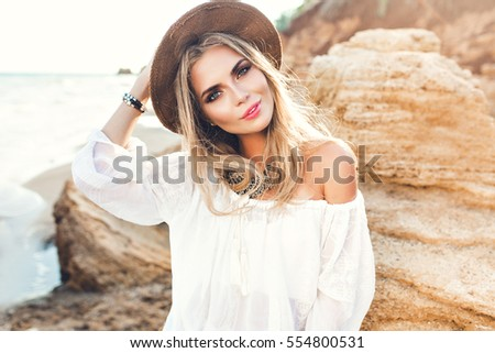Portrait of attractive blonde girl with long hair posing on deserted beach. She wears white shirt, hat, ornamentation. She is smiling to the camera. #554800531
