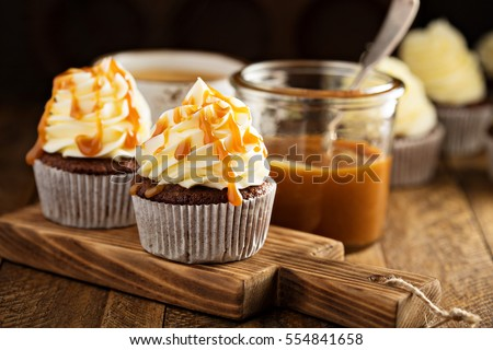 Homemade butterscotch cupcakes with caramel syrup and cream cheese frosting #554841658