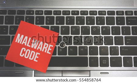 Concept Image of a red sticky note pasted on a keyboard with a message word white in color MALWARE CODE #554858764