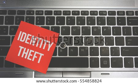 Concept Image of a red sticky note pasted on a keyboard with a message word white in color IDENTITY THEFT #554858824