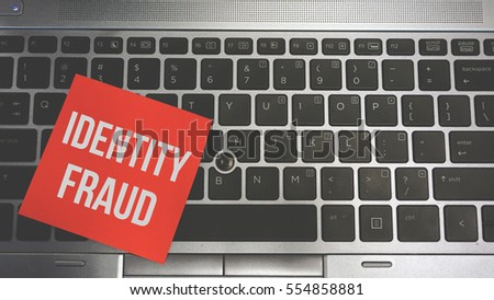 Concept Image of a red sticky note pasted on a keyboard with a message word white in color IDENTITY FRAUD #554858881