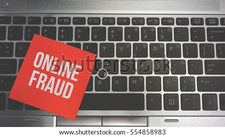 Concept Image of a red sticky note pasted on a keyboard with a message word white in color ONLINE FRAUD #554858983